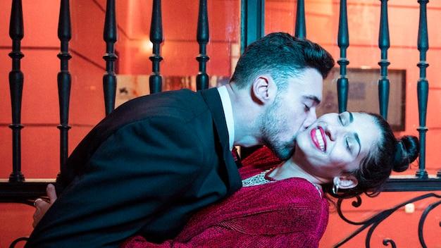 Jeune homme, embrasser, plier, attrayant, femme gaie, près, portes Photo gratuit