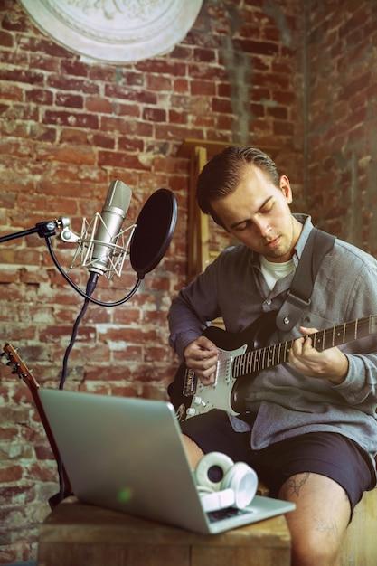 Jeune Homme Enregistrant Une Leçon à La Maison De Blog Vidéo De Musique, Jouant De La Guitare Ou Faisant Un Tutoriel Sur Internet Tout En étant Assis Dans Un Loft Ou à La Maison Concept De Passe-temps, Musique, Art Et Création. Photo gratuit