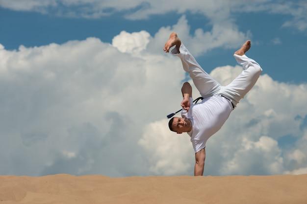 Un jeune homme entraîne la capoeira dans le ciel. un homme effectue un tour acrobatique Photo Premium