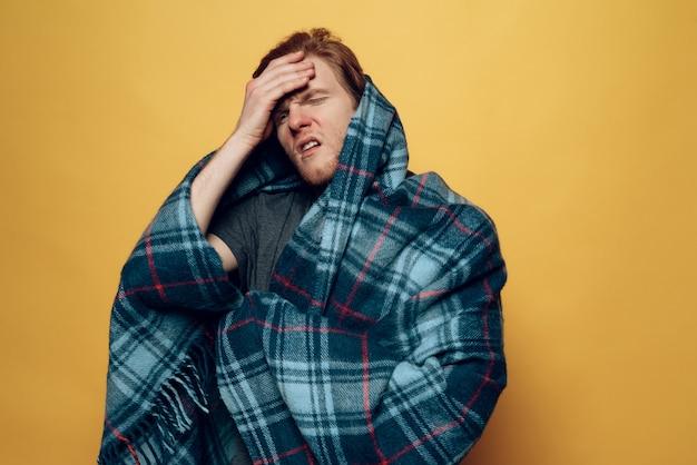 Jeune homme enveloppé dans un plaid toussant avec mal de tête Photo Premium