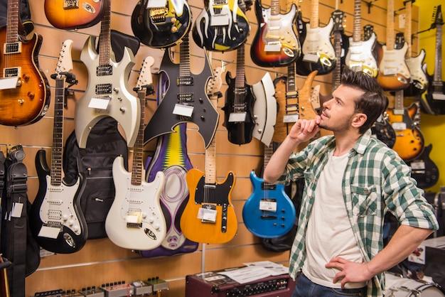 Jeune homme envisage de magasin de musique de guitares électriques. Photo Premium