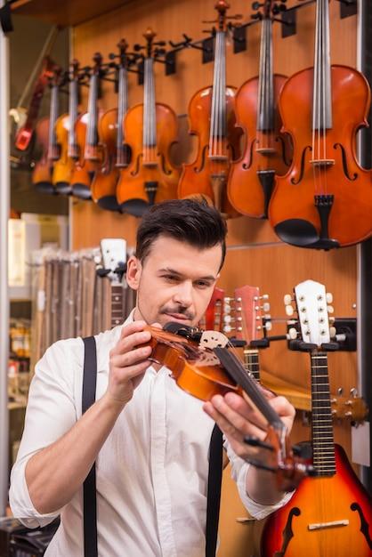 Jeune homme envisage de violon dans un magasin de musique. Photo Premium