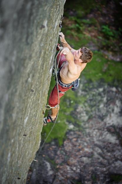 Jeune Homme Escaladant Une Falaise Rocheuse Fixant Des Carabines Et Une Corde Photo Premium