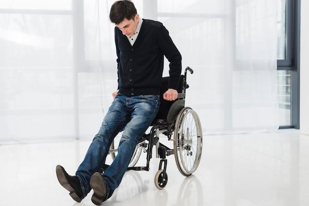Jeune homme essayant de sortir du fauteuil roulant Photo gratuit