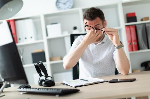 Un jeune homme est assis à une table dans le bureau, enlève ses lunettes et se frotte les yeux. Photo Premium