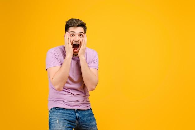 Jeune homme est heureux et excité isolé sur fond jaune Photo Premium