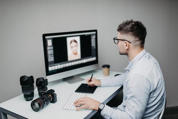 Jeune Homme Est Un Photographe Indépendant Travaillant Sur Un Ordinateur à La Maison Photo Premium