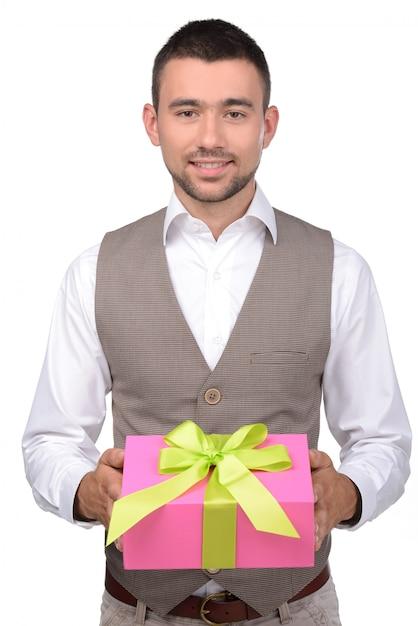 Jeune homme est titulaire d'une boîte avec un cadeau. Photo Premium