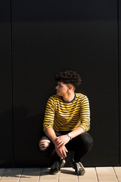 Jeune homme ethnique bouclé assis contre le mur noir Photo gratuit