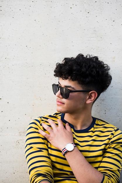 Jeune homme ethnique bouclé dans des lunettes de soleil et sweat rayé Photo gratuit