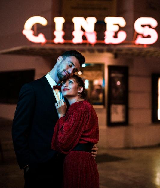 Jeune homme étreignant charmante femme heureuse attrayante sur la rue Photo gratuit