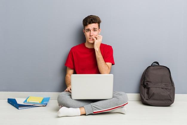 Jeune homme étudiant assis sur le sol de sa maison tenant un ordinateur portable Photo Premium