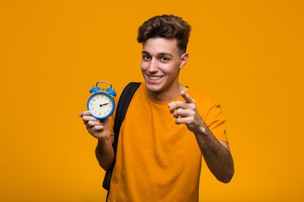 Jeune homme étudiant tenant un réveil criant excité à l'avant. Photo Premium
