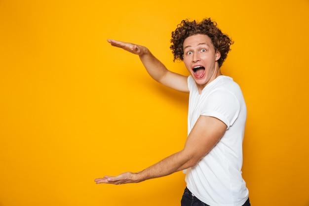 Jeune Homme Excité Aux Cheveux Bouclés Bruns Gesticulant De Côté Et Tenant Un Grand Fond Dans Les Mains Photo Premium