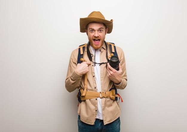 Jeune homme explorateur rousse surpris, qui se sent prospère et prospère. tenant une caméra. Photo Premium