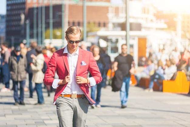 Jeune homme façonné à oslo marchant sur le trottoir bondé Photo Premium