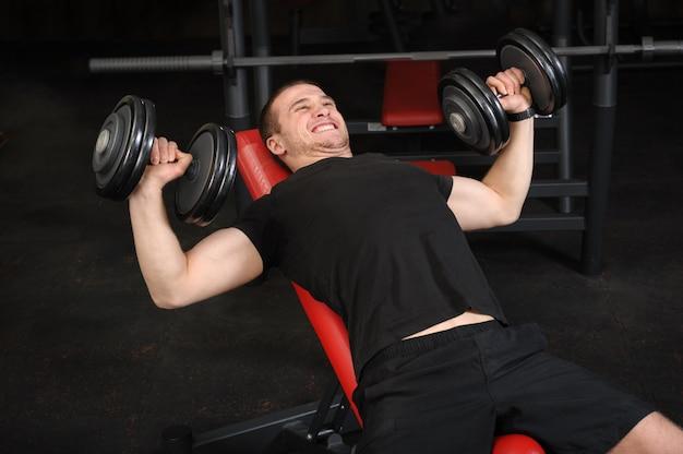 Jeune homme, faire, haltère, inclinaison, banc, presse, entraînement, dans, gymnase Photo Premium