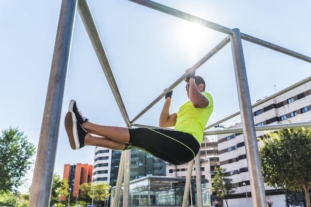 Jeune homme faisant de la callisthénie sur une barre extensible à l'extérieur. Photo Premium