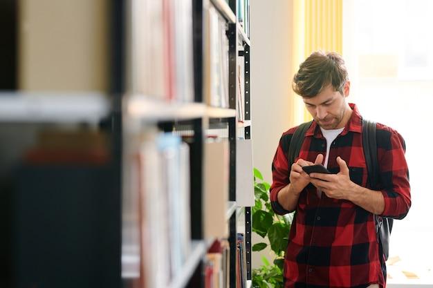 Jeune Homme Faisant Défiler Dans Le Smartphone Par étagère Dans La Bibliothèque Tout En Recherchant Le Nom Du Livre Photo Premium