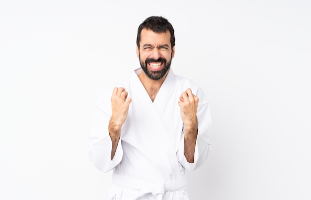 Jeune homme faisant du karaté sur un mur blanc isolé frustré par une mauvaise situation Photo Premium