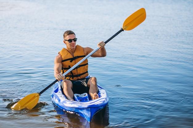 Jeune homme faisant du kayak sur la rivière Photo gratuit