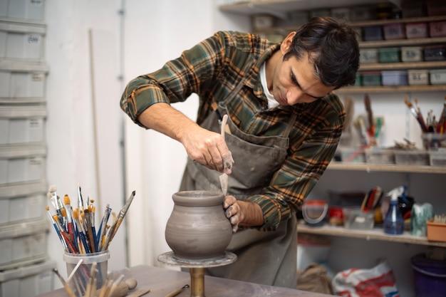 Jeune homme faisant de la poterie en atelier Photo Premium