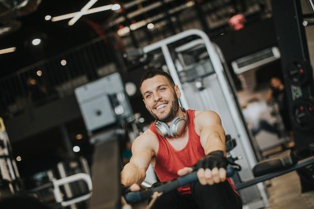 Jeune Homme Faisant Des Séances D'entraînement Sur Le Dos Avec Une Machine D'exercice Dans Un Club De Gym Photo Premium