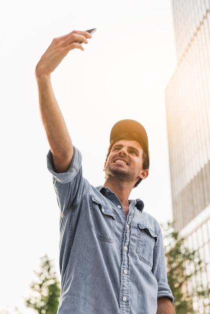 Jeune homme faisant un selfie à l'extérieur Photo gratuit