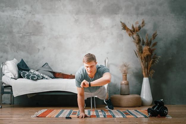 Le Jeune Homme Fait Du Sport à La Maison. Enthousiaste Sportif Aux Cheveux Blonds Tient La Planche Et Regarde Le Chronomètre De L'horloge Sur Sa Main Dans La Chambre Photo Premium