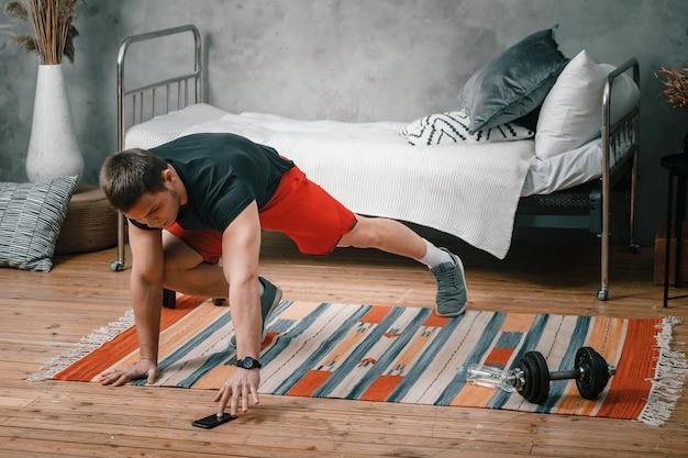 Un Jeune Homme Fait Du Sport à La Maison, Une Séance D'entraînement En Ligne Depuis Le Téléphone. L'athlète Se Précipite, Regarde Un Film Et Les Réseaux Sociaux Dans La Chambre, à L'arrière-plan Il Y A Un Lit, Un Vase, Un Tapis. Photo Premium