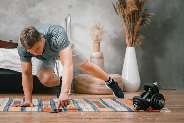 Un Jeune Homme Fait Du Sport à La Maison, Une Séance D'entraînement En Ligne Depuis Le Téléphone. L'athlète Se Précipite, Regarde Un Film Et Les Réseaux Sociaux Dans La Chambre Photo Premium