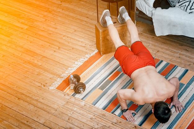 Le Jeune Homme Fait Du Sport à La Maison. Sportif Aux Cheveux Blac Fait Des Pompes Sur Un Tapis Dans La Chambre, Vue Du Dessus Photo Premium