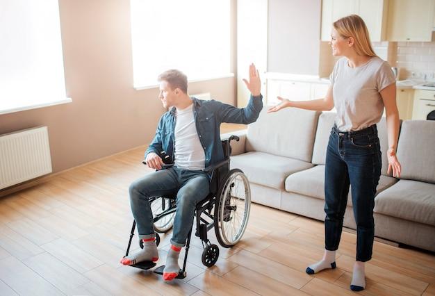 Jeune Homme En Fauteuil Roulant Discuter Avec Sa Petite Amie. Handicap Et Inclusivité. Personne Ayant Des Besoins Spéciaux. Bouleversé Et Malheureuse Jeune Femme. Photo Premium