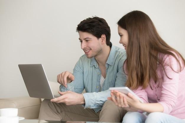 Jeune homme et femme à l'aide d'un ordinateur portable Photo gratuit
