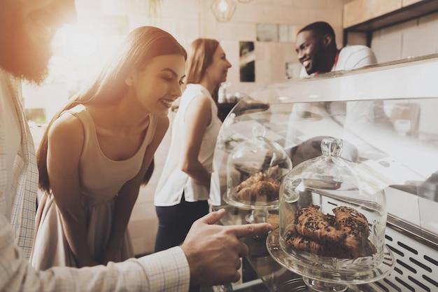 Jeune homme et une femme choisissent des pâtisseries dans un café Photo Premium