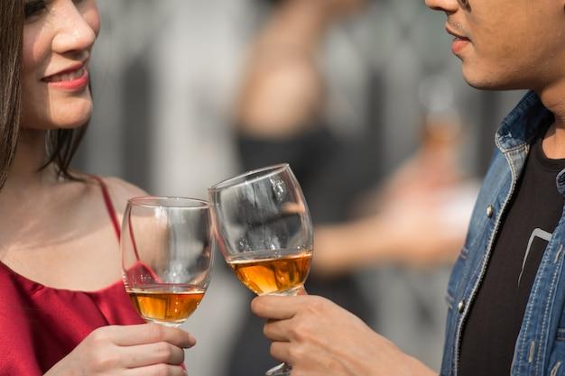 Jeune homme et femme à date en restaurant debout tenant des verres d'alcool et se regardant. Photo Premium