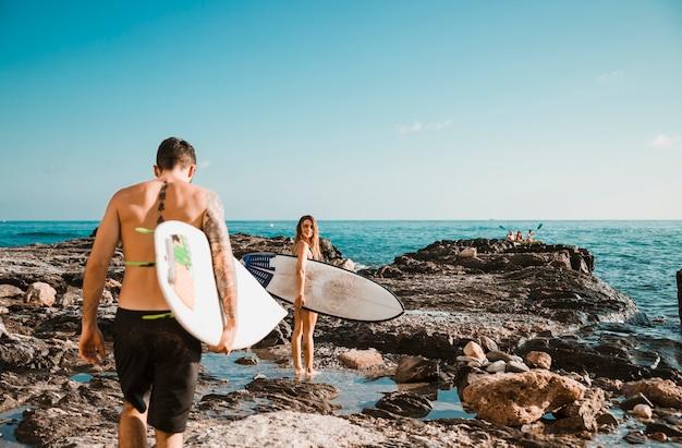 Jeune homme et femme avec des planches de surf sur le rivage de pierre près de l'eau Photo gratuit