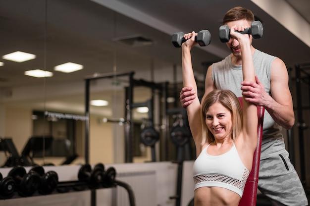 Jeune homme et femme s'entraînant au gymnase Photo gratuit