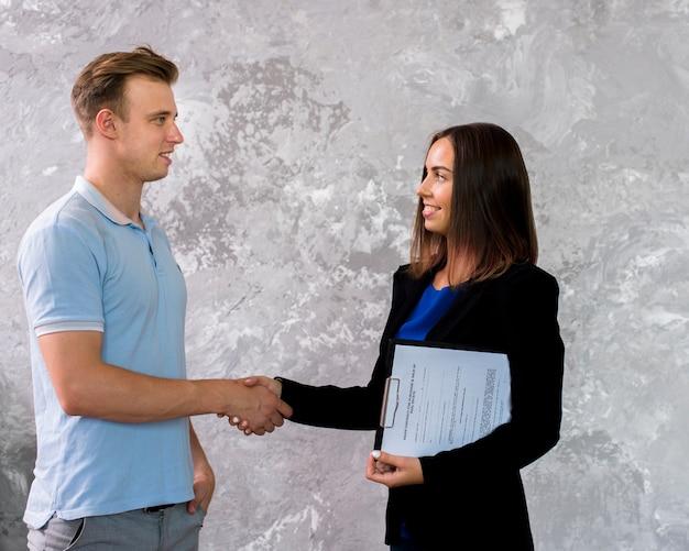 Jeune homme et femme se serrant la main Photo gratuit
