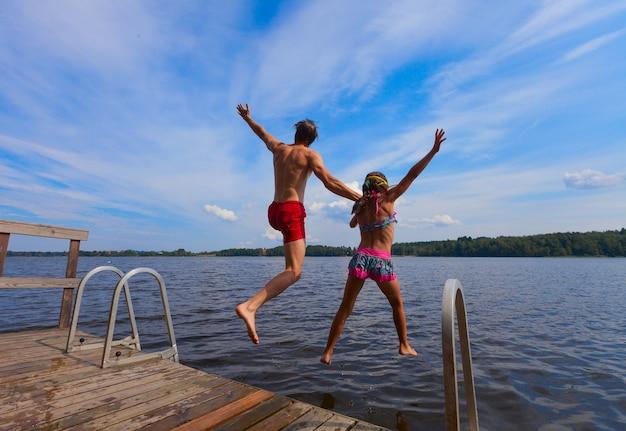 Jeune homme et fille sautant dans l'eau Photo Premium