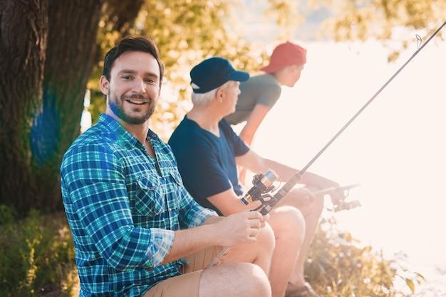 Jeune homme avec fils et père pêchant sur la rivière. Photo Premium