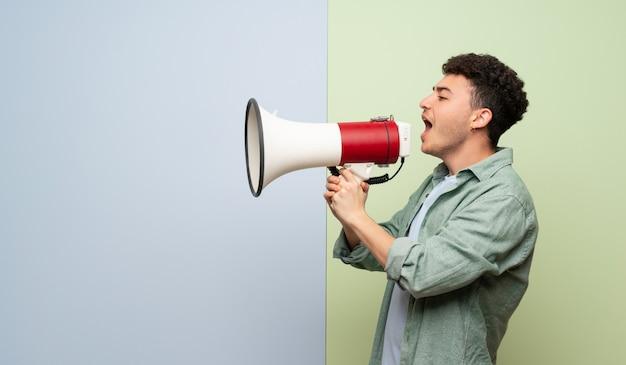 Jeune homme sur fond bleu et vert criant à travers un mégaphone Photo Premium