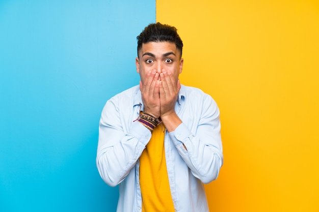 Jeune homme sur fond coloré isolé avec une expression faciale surprise Photo Premium