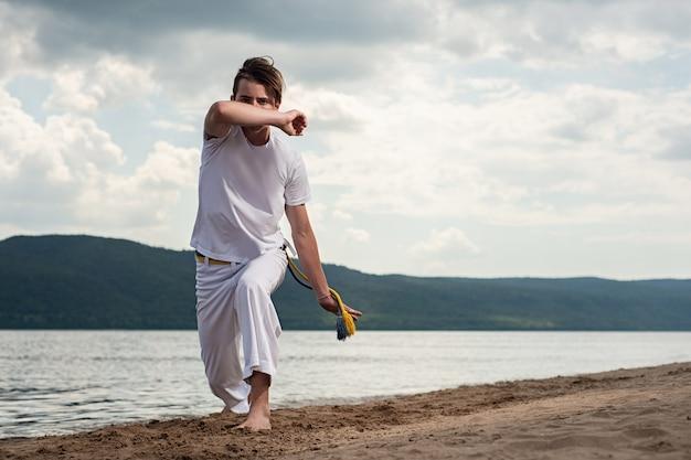 Jeune Homme Forme La Capoeira Sur Fond De Ciel. Un Homme Exécute Le Coup De Pied Martial Dans Le Saut Photo Premium