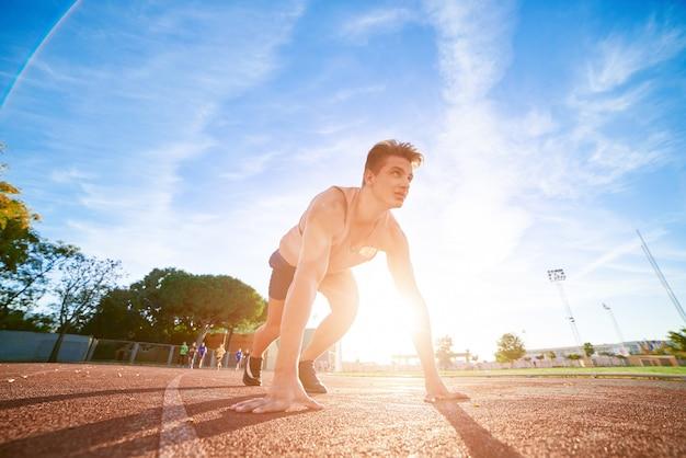 Jeune homme en forme et confiant en position de départ, prêt à courir Photo Premium