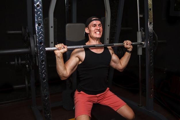 Jeune homme forme son dos dans la salle de gym. Photo Premium