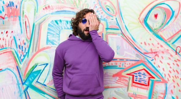 Jeune homme fou barbu ayant l'air endormi, ennuyé et bâillant, avec un mal de tête et une main couvrant la moitié du visage contre un mur de graffitis Photo Premium