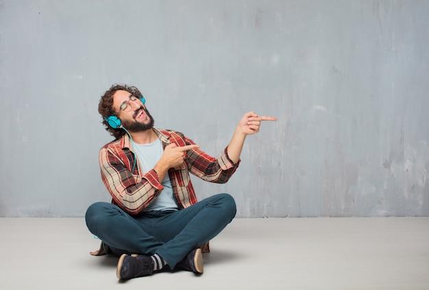 Jeune homme fou fou imbécile pose écoute de la musique avec un casque Photo Premium