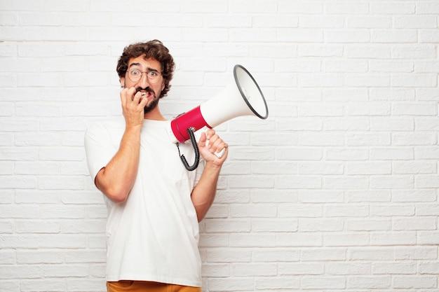 Jeune Homme Fou Avec Un Mégaphone Contre Le Mur De Briques. Photo Premium