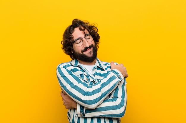 Jeune homme fou se sentant amoureux, souriant, câlinant et s'embrassant lui-même, restant célibataire, étant un mur jaune égoïste et égocentrique Photo Premium